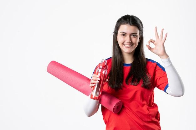 Vue de face souriante jeune femme en vêtements de sport avec tapis de yoga