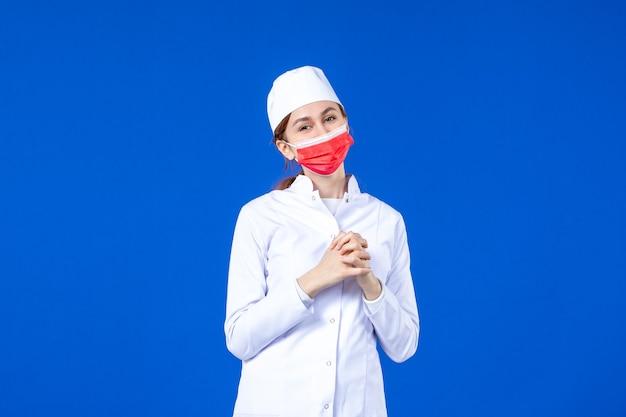 Vue de face souriante jeune infirmière en costume médical avec masque de protection rouge sur bleu