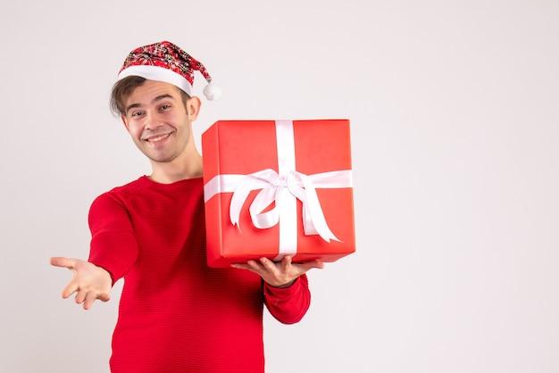 Vue de face sourit jeune homme avec bonnet de noel donnant la main sur blanc