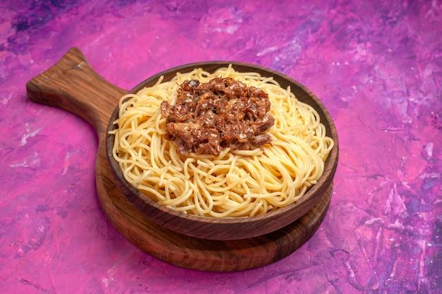 Vue de face des spaghettis cuits avec de la viande hachée sur un plat de pâte de table rose assaisonnement pour pâtes