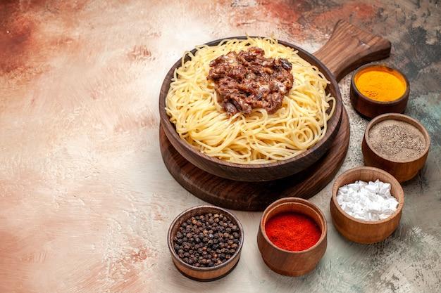 Vue de face des spaghettis cuits avec de la viande hachée sur un plat de table léger pâte de viande de pâtes