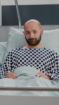 Vue de face d'un spécialiste médical afro-américain et d'un homme malade ayant une conférence par vidéoconférence en ligne avec un médecin lors d'une consultation sur la maladie dans une salle d'hôpital