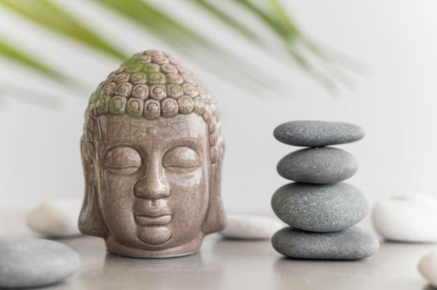 Vue de face de la statue de la tête de bouddha avec des pierres