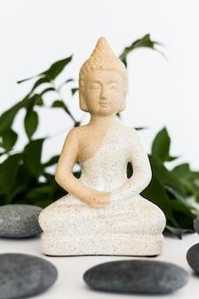 Vue de face de la statuette de bouddha avec des pierres