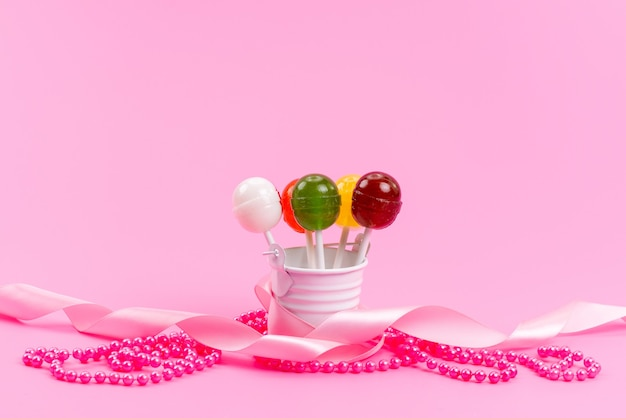Une vue de face sucettes colorées à l'intérieur blanc, seau sur rose, bonbons de confiserie sucrée sucre