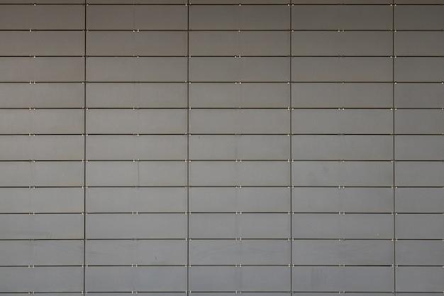 Vue de face d'une surface grise constituée de petites tuiles métalliques