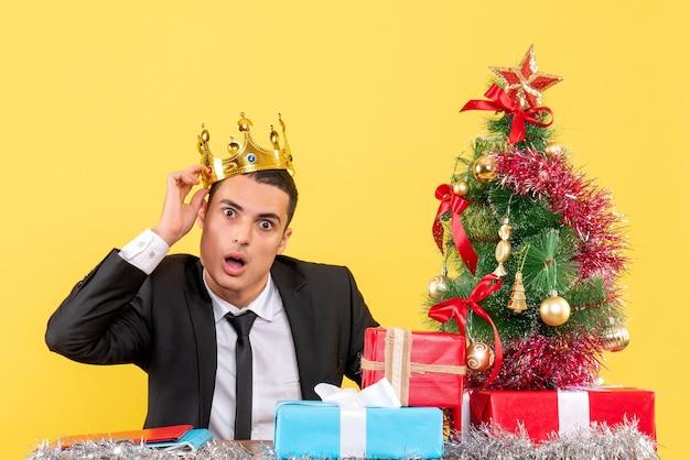 Vue de face surpris bel homme avec couronne assis à la table arbre de noël et cadeaux