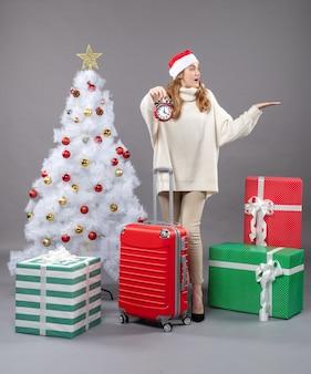 Vue de face surpris fille blonde avec bonnet de noel tenant un réveil rouge près de l'arbre de noël blanc et valise rouge