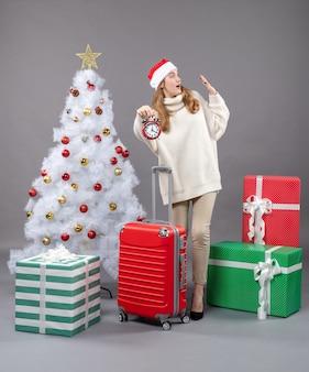 Vue de face surpris fille blonde avec bonnet de noel tenant un réveil rouge près de l'arbre de noël blanc