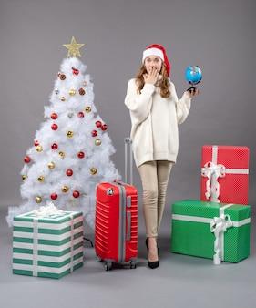 Vue de face surpris fille blonde avec bonnet de noel tenant valise rouge regardant globe