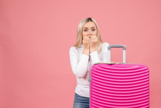 Vue de face surpris jeune femme debout derrière une grosse valise