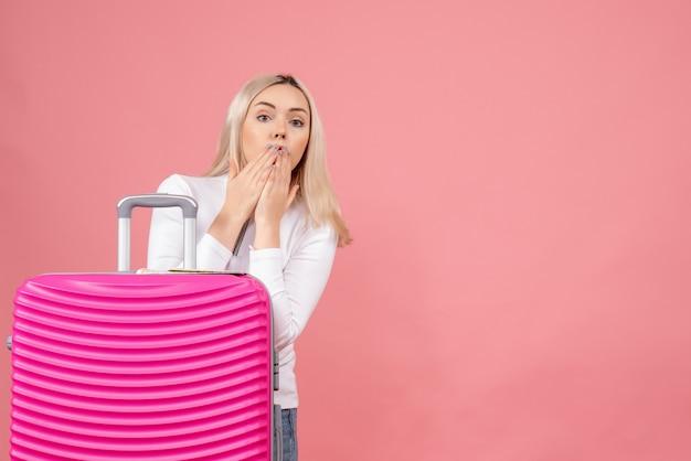 Vue de face surpris jeune femme debout derrière une valise rose