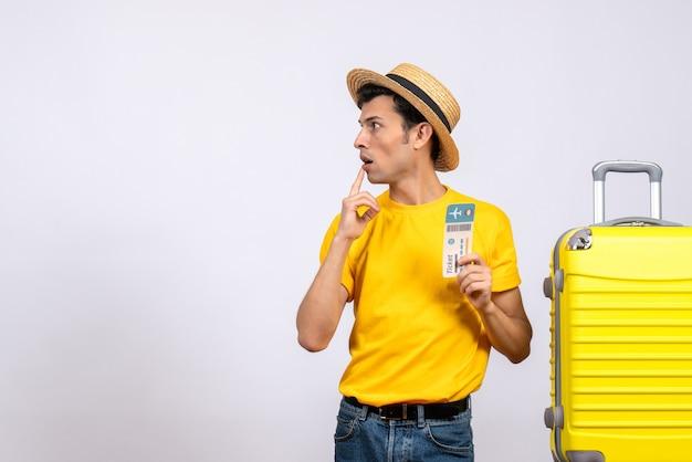 Vue de face surpris jeune homme en t-shirt jaune debout près de la valise jaune en regardant quelque chose