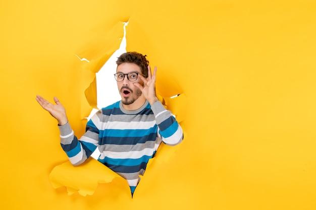 Vue de face surpris jeune homme tenant ses lunettes lorgnant à travers le trou dans le mur de papier jaune