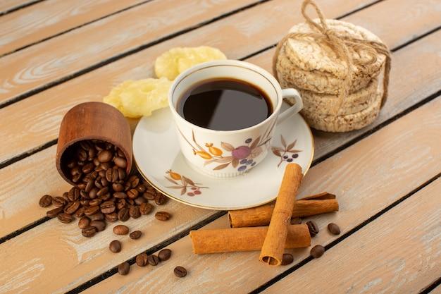 Une vue de face tasse de café chaud et fort avec des graines de café brun frais cannelle et craquelins sur le bureau rustique crème café graine photo grain