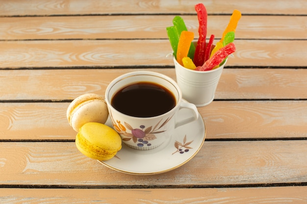 Une vue de face tasse de café chaud et fort avec des macarons français et de la marmelade sur le bureau rustique de couleur crème boire du café photo forte