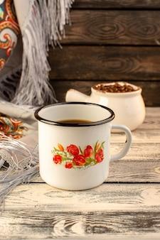 Vue de face d'une tasse de café avec des graines de café brun sur le bureau en bois