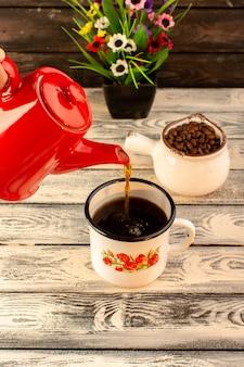 Vue de face de la tasse chaude versant de la bouilloire rouge des graines de café brun et des fleurs sur le bureau en bois
