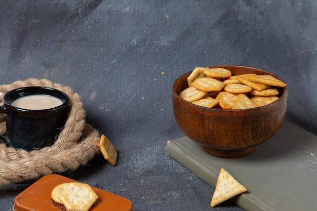 Vue de face de la tasse de lait avec des chips et des craquelins sur la surface grise