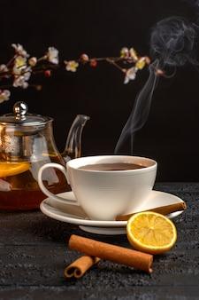 Vue de face tasse de thé au citron cannelle et bouilloire sur surface grise