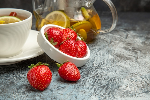 Vue de face tasse de thé aux fraises sur la surface sombre de la baie de thé aux fruits