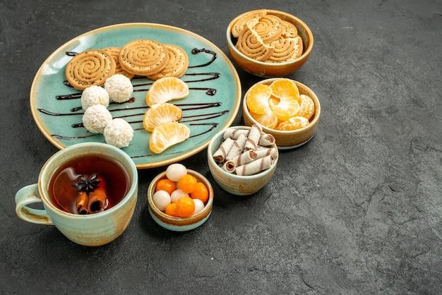 Vue de face tasse de thé avec des biscuits et des bonbons sur la table grise biscuit gâteau biscuit thé