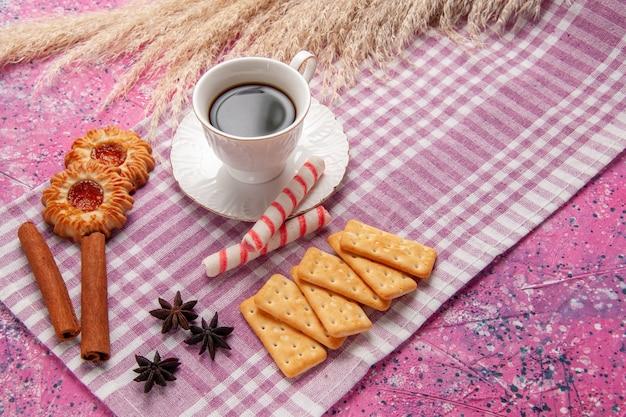 Vue de face tasse de thé avec des biscuits à la cannelle et des craquelins sur le bureau rose biscuit sucre sweet bake