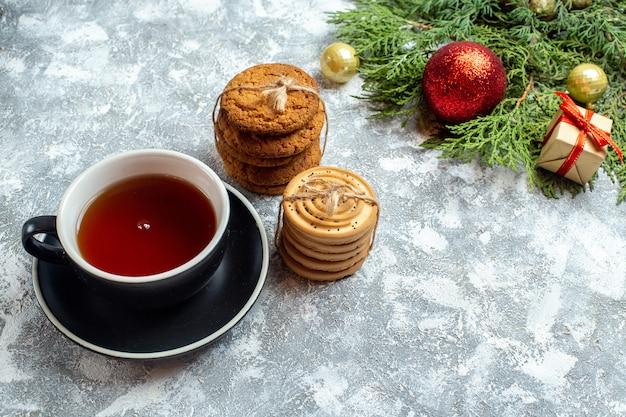 Vue de face tasse de thé avec des biscuits et des jouets sur fond blanc