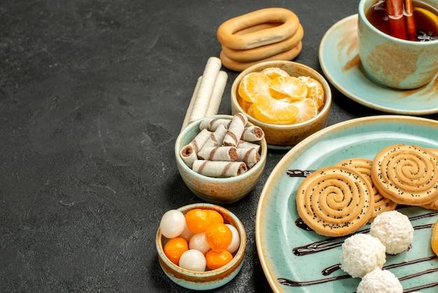 Vue de face tasse de thé avec des biscuits et des mandarines sur bureau gris biscuit gâteau biscuit thé