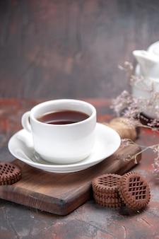 Vue de face tasse de thé avec des biscuits sur la table sombre biscuit noir