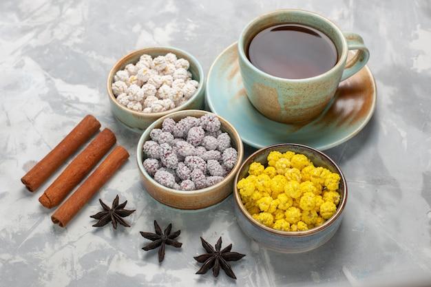 Vue de face tasse de thé avec des bonbons de sucre et de cannelle sur une surface blanche