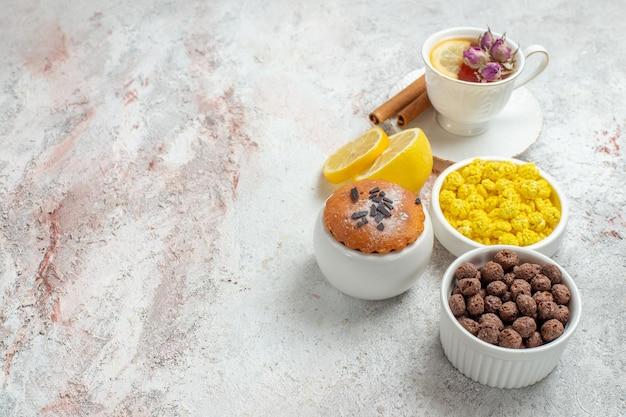 Vue de face tasse de thé avec des bonbons et des tranches de citron sur un espace blanc