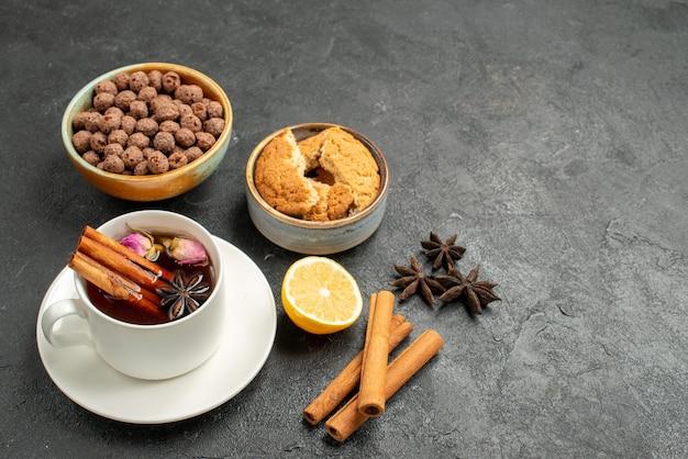Vue de face tasse de thé à la cannelle sur la cérémonie de boisson au thé de fond gris foncé sucré