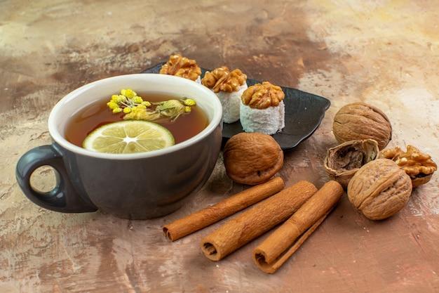 Vue de face tasse de thé à la cannelle et confitures sur le bureau léger