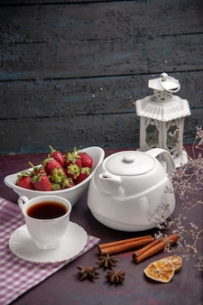 Vue de face tasse de thé avec de la cannelle et des fraises sur une surface sombre boire du thé couleur fruits