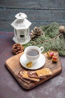 Vue de face tasse de thé avec des cônes et des tranches de gâteau sur un espace sombre