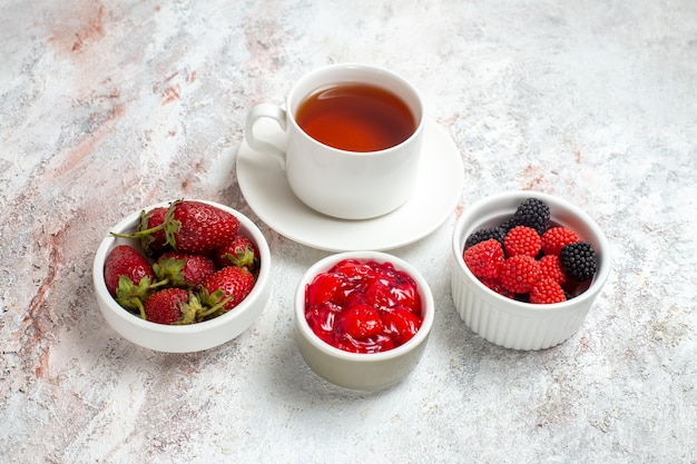 Vue de face tasse de thé avec confitures et confiture sur espace blanc