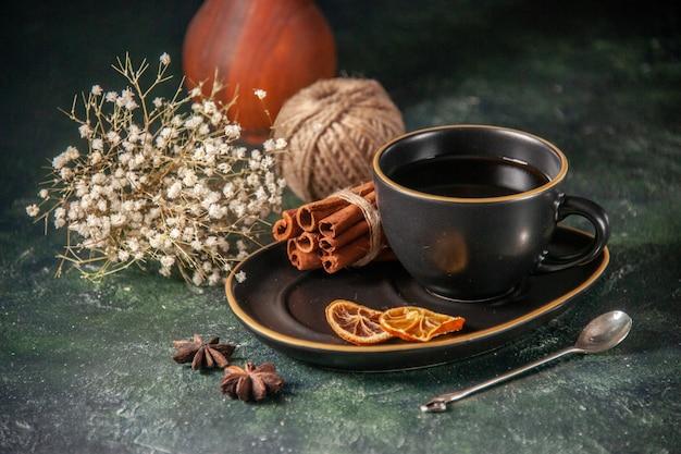 Vue de face tasse de thé dans une tasse noire et une assiette avec de la cannelle sur la surface sombre de la cérémonie du sucre verre petit déjeuner dessert gâteau sucré