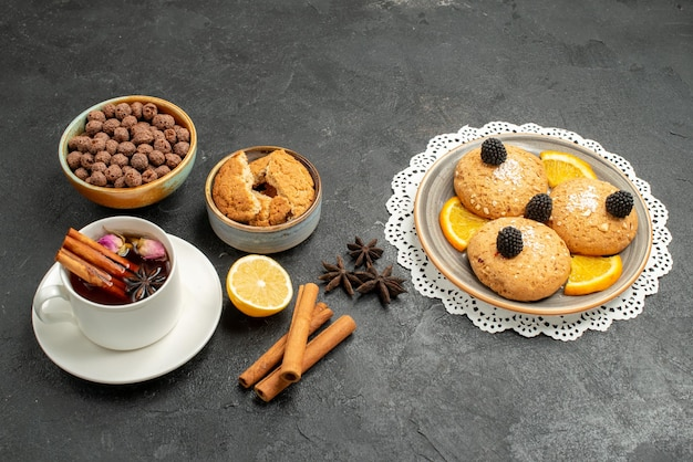 Vue de face tasse de thé avec de délicieux biscuits sur fond gris foncé cérémonie de boisson au thé sucré