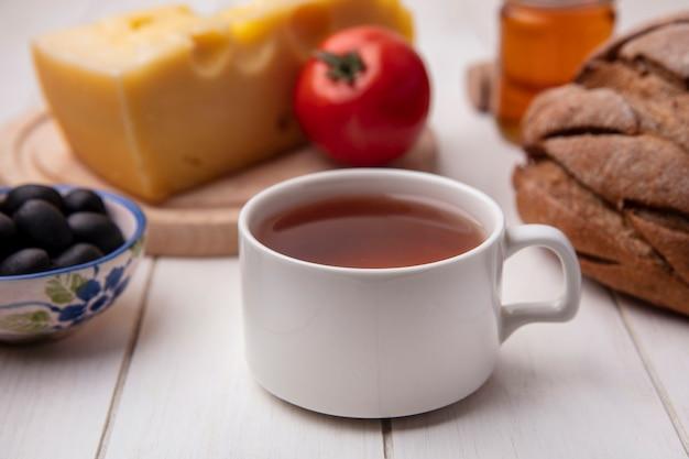Vue de face tasse de thé avec du fromage tomate olives sur un support et une miche de pain noir sur fond blanc