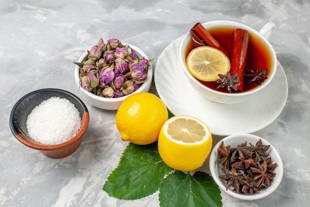 Vue de face tasse de thé avec des fleurs et du citron sur une surface blanche