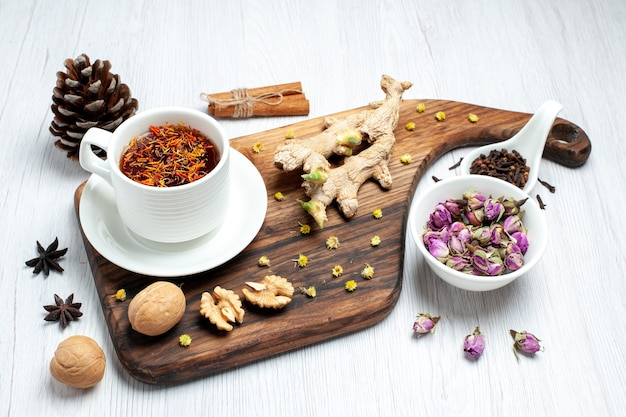 Vue de face tasse de thé avec des fleurs séchées et des noix sur fond blanc boisson thé écrou