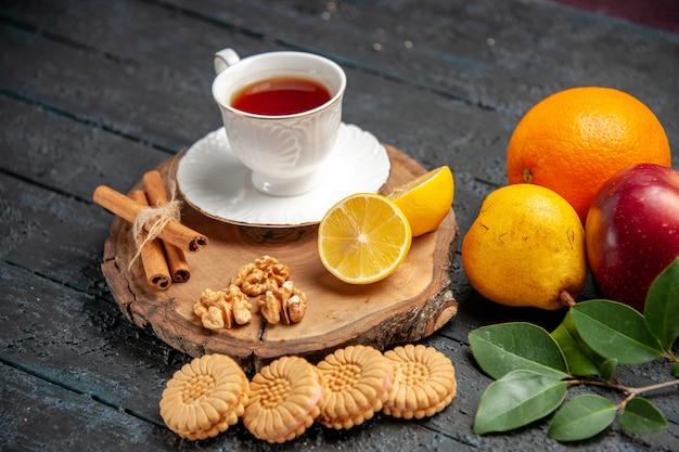 Vue de face tasse de thé avec des fruits et des biscuits sur un sol sombre