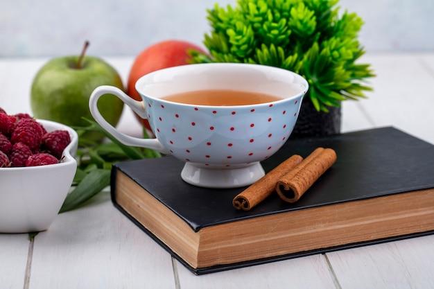 Vue de face d'une tasse de thé sur un livre avec des framboises à la cannelle et des pommes sur une surface blanche