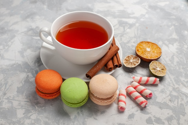 Vue de face tasse de thé avec des macarons français sur un bureau léger