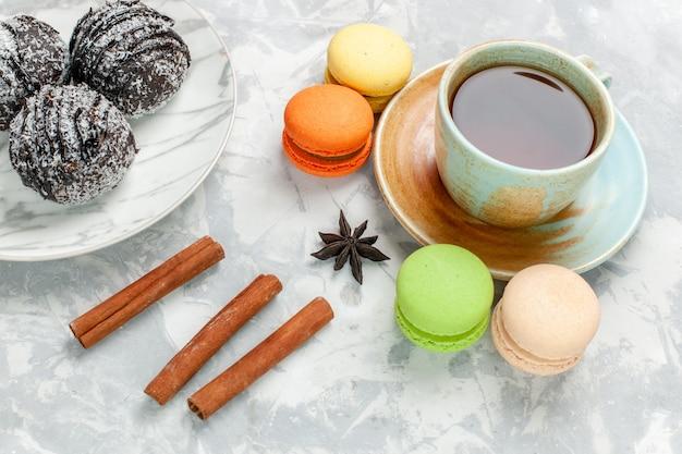 Vue de face tasse de thé avec des macarons gâteaux au chocolat et cannelle sur bureau blanc cuire gâteau biscuit sucre tarte sucrée