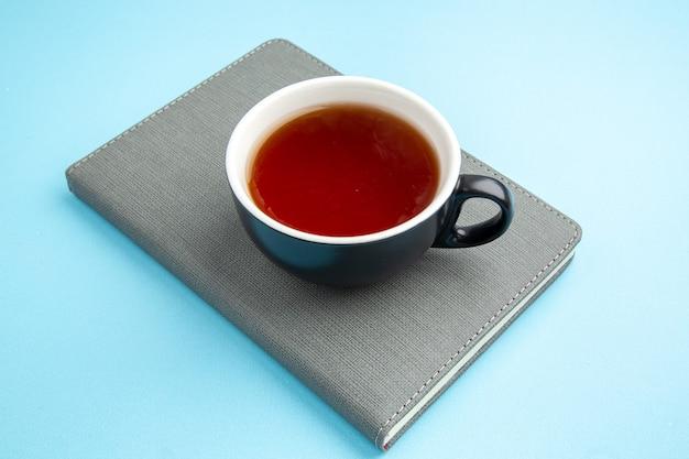 Vue de face d'une tasse de thé noir sur un cahier gris sur une surface bleue