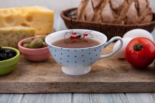 Vue de face tasse de thé avec des œufs de poule à la tomate et olives sur un support