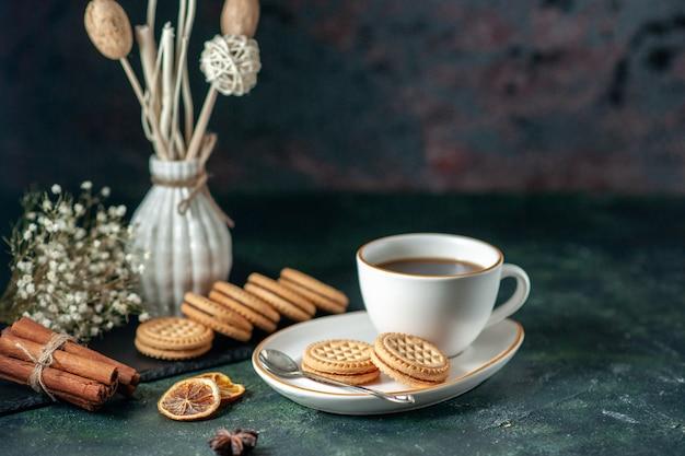 Vue de face tasse de thé avec de petits biscuits sucrés dans une assiette blanche sur la surface sombre du pain boisson couleur de la cérémonie du petit-déjeuner en verre du matin