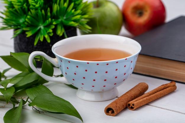 Vue de face d'une tasse de thé avec des pommes à la cannelle et un livre sur une surface blanche